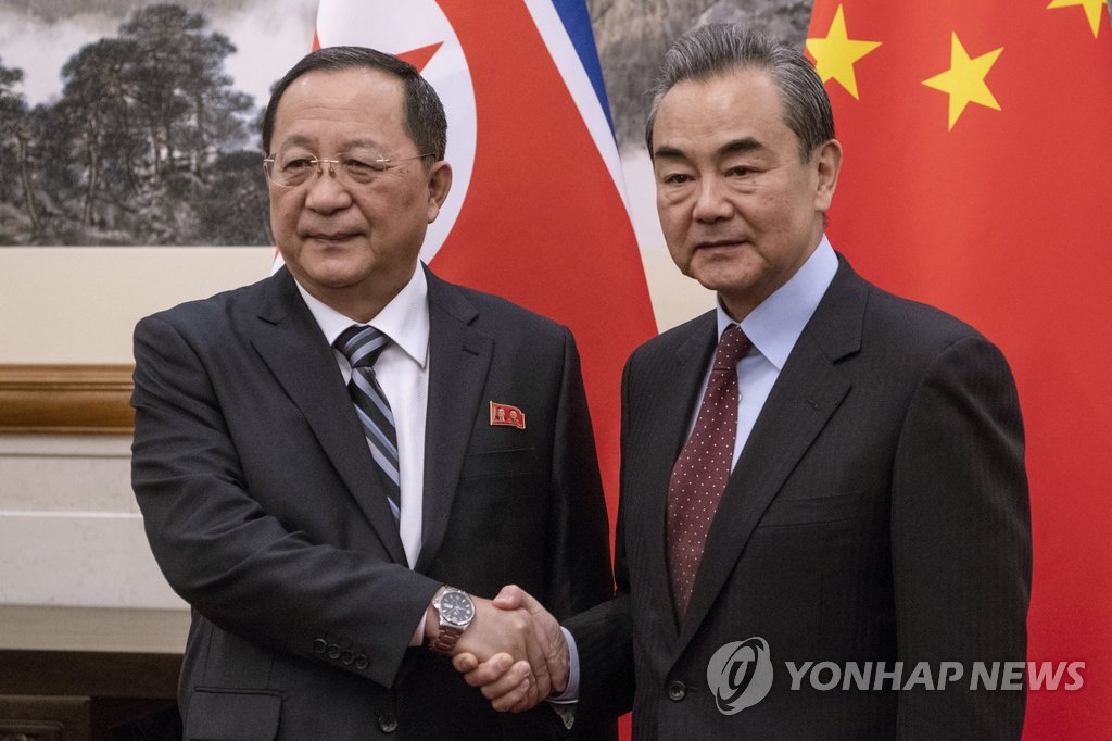 This AP photo shows North Korean Foreign Minister Ri Yong-ho (L) shaking hands with his Chinese counterpart, Wang Yi, in Beijing on Dec. 7, 2018. (Yonhap)