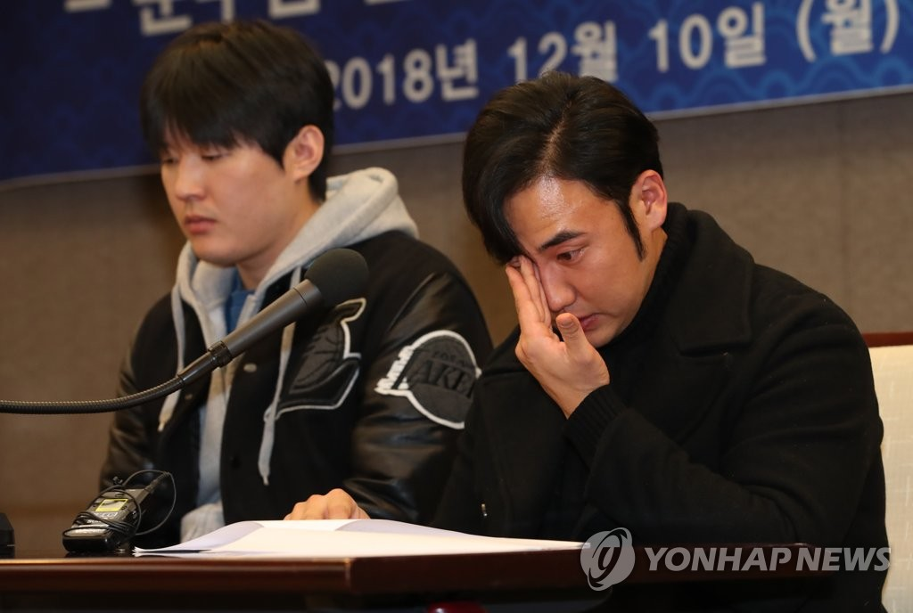 Moon Woo-ram (R), former outfielder of the Nexen Heroes, wipes away tears during a press conference on Dec. 10, 2018, in Seoul, where he claimed he was wrongfully convicted of match fixing. (Yonhap)