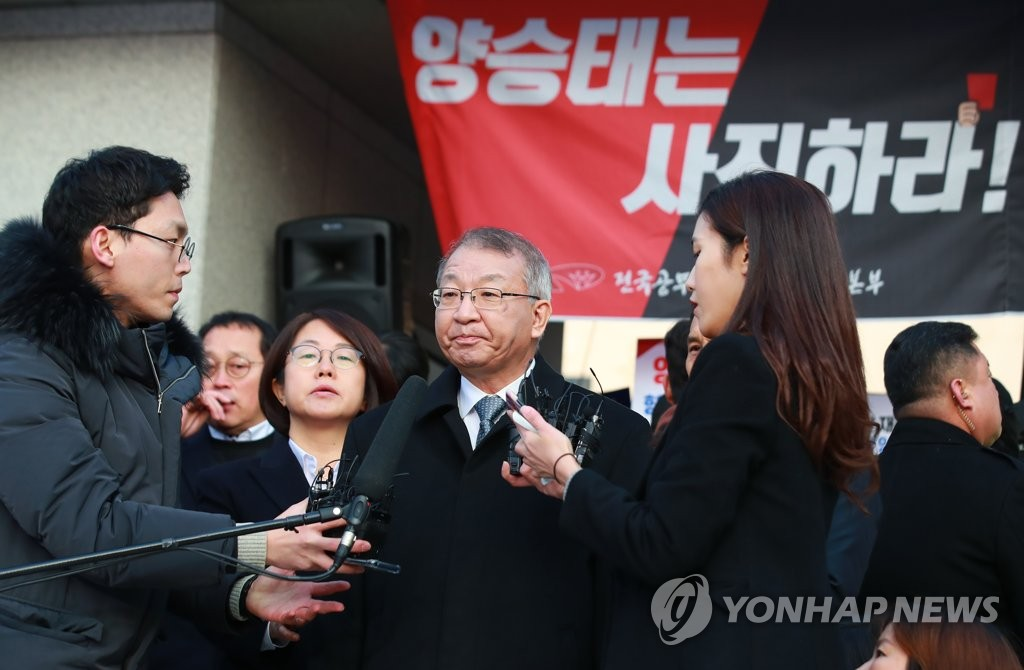 Former Supreme Court Chief Justice Yang Sung-tae (C) answers questions from reporters in front of the top court building in southern Seoul on Jan. 11, 2019, ahead of his questioning by the prosecution over power abuse allegations. (Yonhap)
