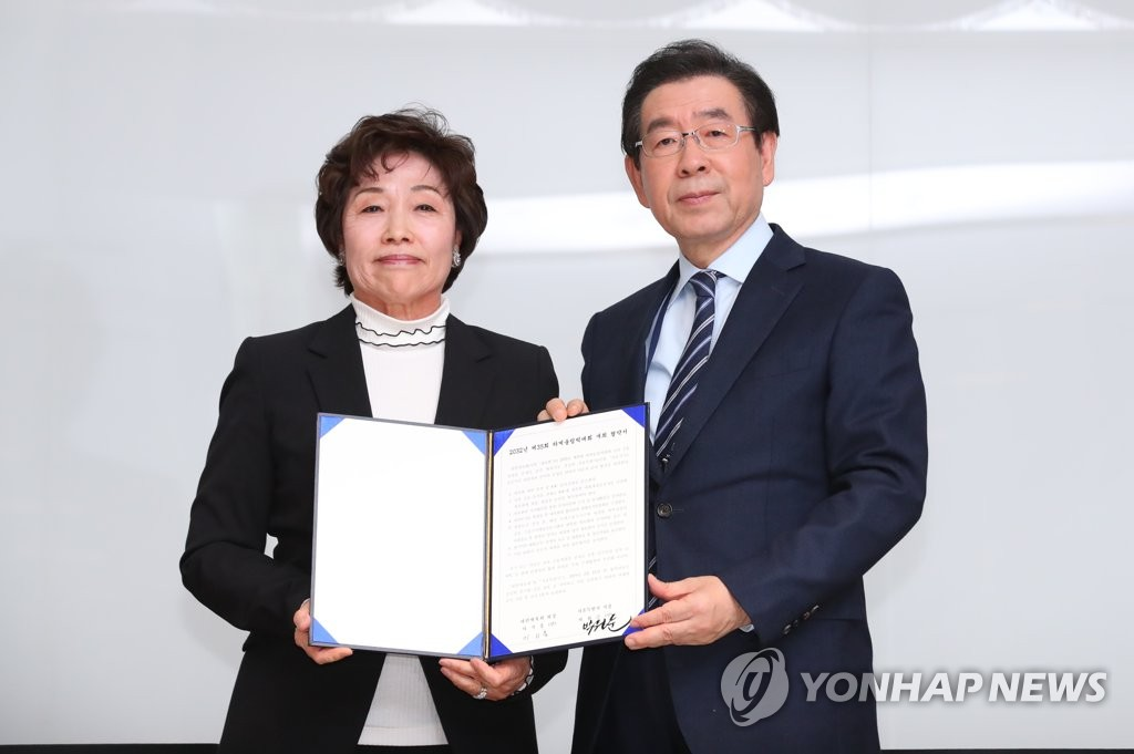 Seoul Mayor Park Won-soon (R) and Korean Sport & Olympic Committee (KSOC) Vice President Kim Young-chae pose with a document appointing Seoul as the South Korean candidate city for a joint 2032 Summer Olympics bid with North Korea after a KSOC vote at the Jincheon National Training Center in Jincheon, 90 kilometers south of Seoul, on Feb. 11, 2019. (Yonhap)