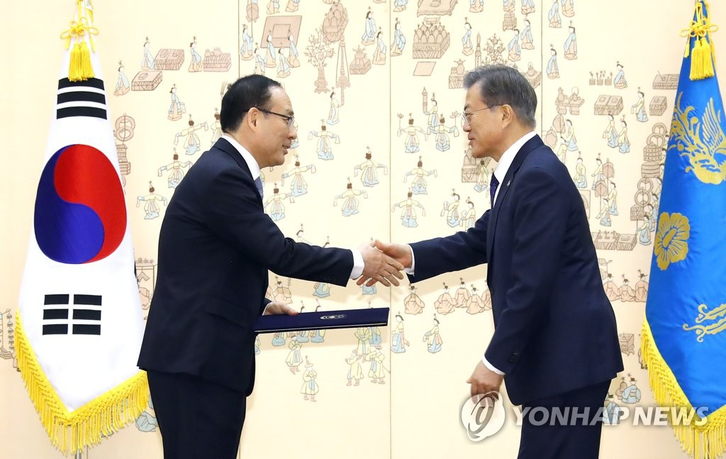 President Moon Jae-in (R) shakes hands with Oh Se-jung, new head of the state-run Seoul National University, after appointing Oh to the university post in a ceremony held at his office Cheong Wa Dae in Seoul on Feb. 20, 2019. (Yonhap)