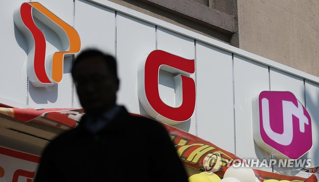 A pedestrian passes by a smartphone shop with logos of South Korea's three telecom operators in Seoul on April 4, 2019. SK Telecom Co., KT Corp. and LG Uplus Corp. activated Samsung's Galaxy S10 5G on April 3, 2019, claiming to be the first in the world to start commercial services of the new network. (Yonhap)