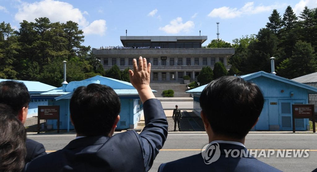 A member of the leadership of South Korea's ruling Democratic Party waves towards a group of North Korean students during a visit to the inter-Korean truce village of Panmunjom on May 31, 2019. The group was on a security tour of the village to mark the first anniversary of the April 27 joint declaration between South Korean President Moon Jae-in and North Korean leader Kim Jong-un. (Pool photo) (Yonhap)