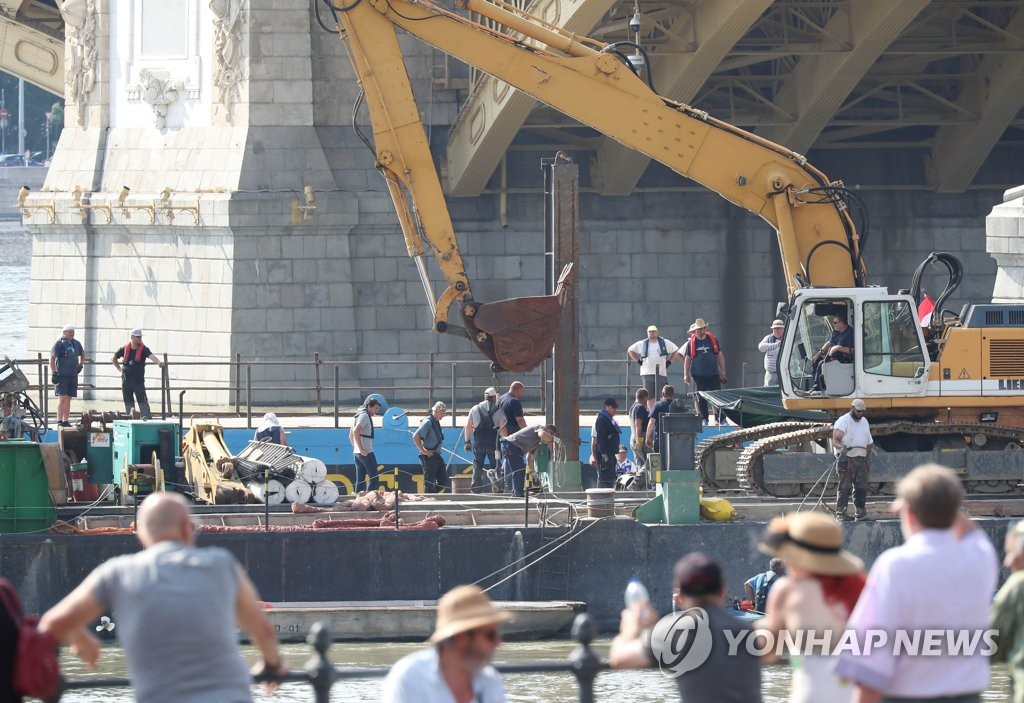 This photo, taken on June 9, 2019, shows Hungarian officials preparing to lift a sunken tourist boat out of the Danube River near Margaret Bridge in Budapest. (Yonhap)