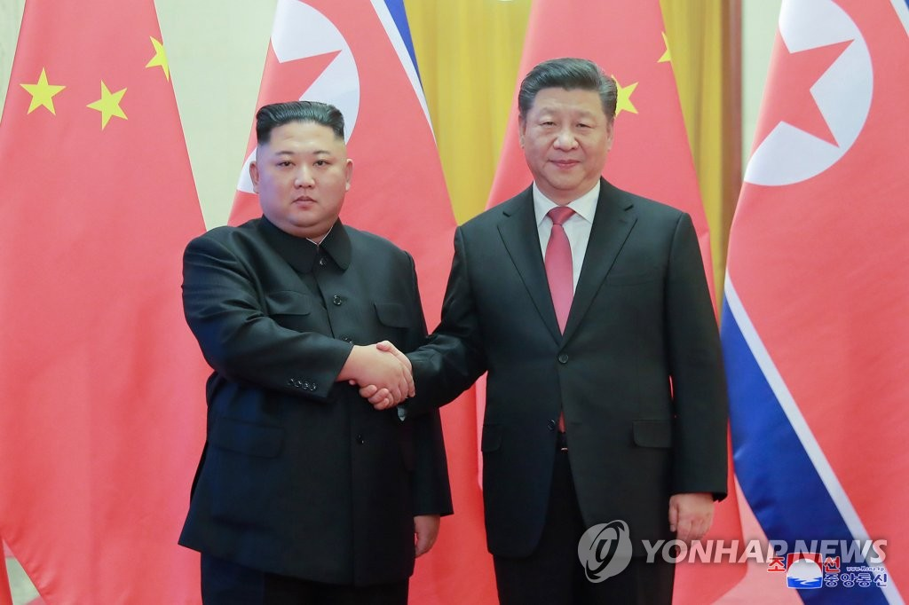 This file photo shows North Korean leader Kim Jong-un (L) and Chinese President Xi Jinping posing for a photo during Kim's fourth trip to China in January 2019. (Yonhap)