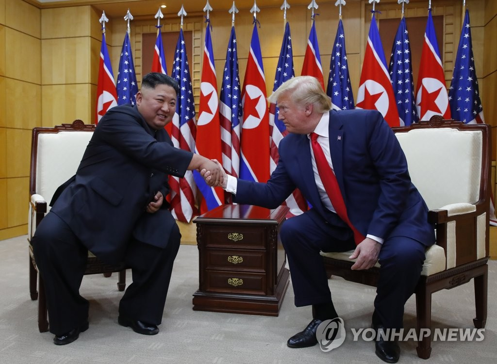 U.S. President Donald Trump (R) and North Korean leader Kim Jong-un shake hands as they meet at the Freedom House on the southern side of the truce village of Panmunjom in the Demilitarized Zone, which separates the two Koreas, on June 30, 2019. (Yonhap)