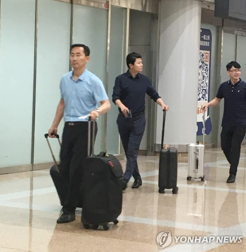 Ri Yong-pil (L), the North's deputy envoy to the United Nations, walks through an airport in Beijing on July 18, 2019, apparently having flown from Pyongyang. (Yonhap)