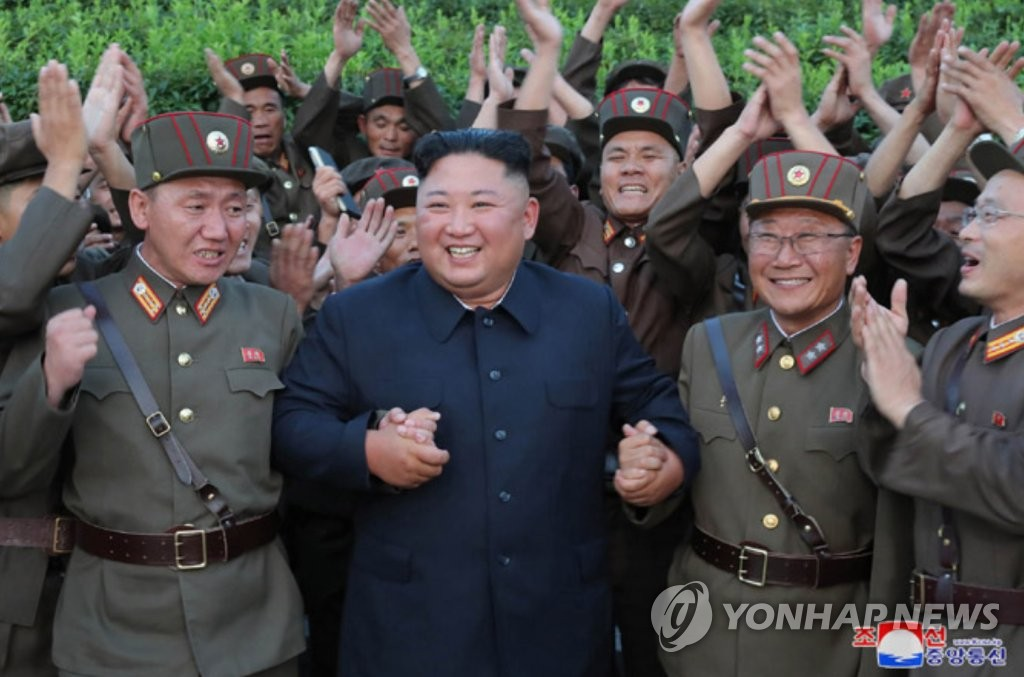 North Korean leader Kim Jong-un (C) holds hands with military officials after supervising the launch of new tactical guided missiles on Aug. 6, 2019, in this photo released by the Korean Central News Agency the next day. (For Use Only in the Republic of Korea. No Redistribution) (Yonhap)