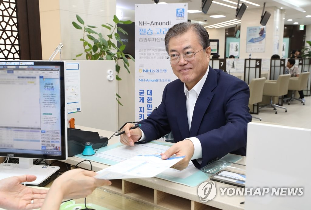 President Moon Jae-in submits a document on his plan to invest in a stock fund operated by NH-Amundi Asset Management Co. at the headquarters of NH Nonghyup Bank in Seoul on Aug. 26, 2019. (Yonhap)