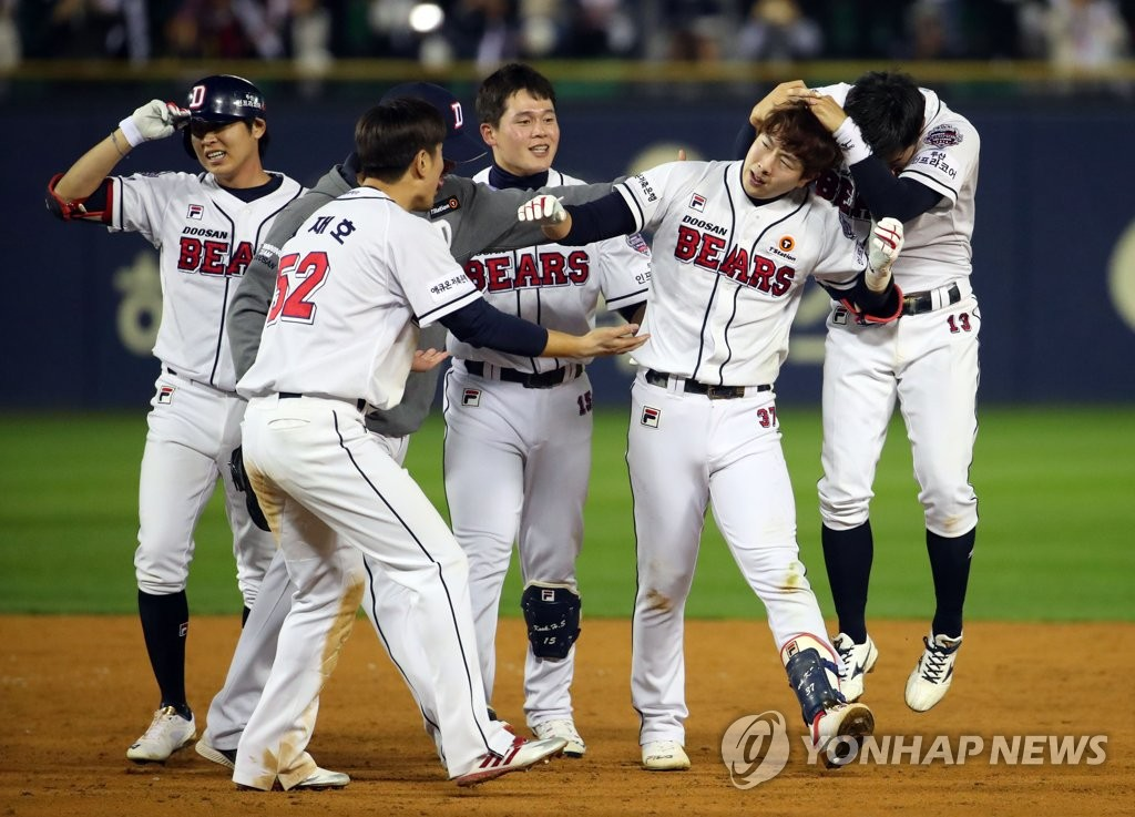 Park Kun-woo of the Doosan Bears (2nd from R) is mobbed by teammates after delivering a walk-off single in the bottom of the ninth inning against the Kiwoom Heroes in Game 2 of the Korean Series at Jamsil Stadium in Seoul on Oct. 23, 2019. The Bears won the game 6-5. (Yonhap)