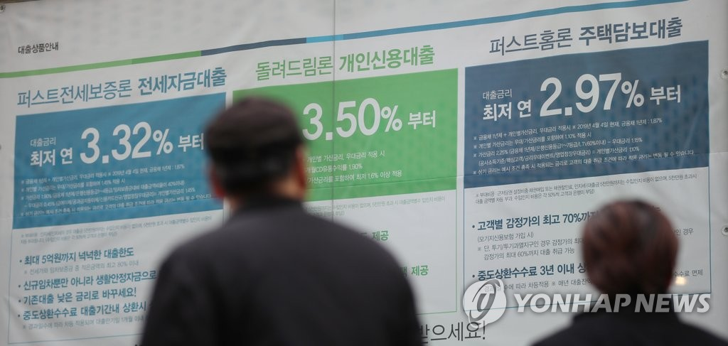 In the file photo, taken Nov. 10, 2019, consumers examine bank lending rates on a wall post at a Seoul bank. (Yonhap)