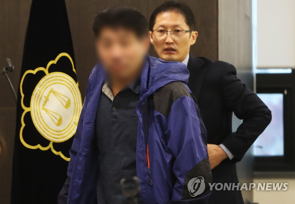 A man whose face has been blurred to protect his identity enters a hall in Suwon, south of Seoul, for a press briefing to claim his innocence and announce his plan to file for a retrial of the Lee Chun-jae serial murder case on Nov. 13, 2019. (Yonhap)