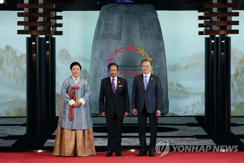 "President Moon Jae-in (R) and first lady Kim Jung-sook (L) pose for a photo with Hassanal Bolkiah, the sultan of Brunei, who attended a welcoming banquet at a hotel in the southeastern port city of Busan on Nov. 25, 2019. A hologram of a large bronze bell from the Unified Silla era (676-935), known as the ""Bell of King Seongdeok,"" was installed at the entrance where Moon and Kim received guests. (Yonhap)"