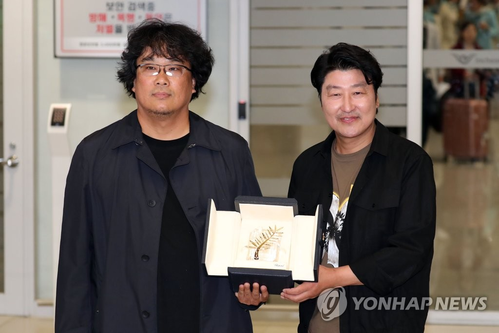 South Korean director Bong Joon-ho (L) and actor Song Kang-ho (R) show off the Palme d'Or award during a meeting with reporters at Incheon International Airport, west of Seoul, on May 27, 2019, upon returning home from Cannes, France. (Yonhap)