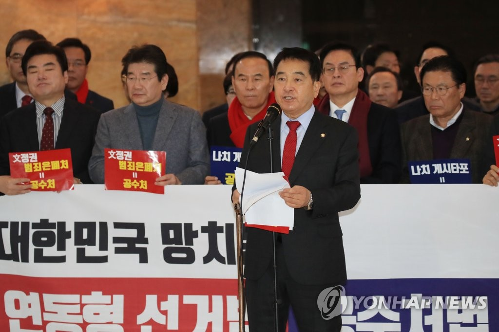 In this photo taken on Dec. 30, 2019, the main opposition Liberty Korea Party's floor leader Rep. Shim Jae-chul (front) announces party members' resolution to resign en masse in protest against the passage of the corruption probe unit bill aimed at reforming the prosecution at the National Assembly in Seoul. (Yonhap)