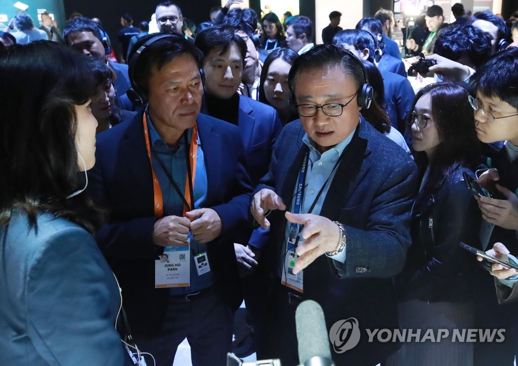 Koh Dong-jin (R), President and CEO of Samsung's IT & Mobile Communication division, explains the company's products to SK Telecom CEO Park Jung-ho at Samsung booth at Consumer Electronics Show (CES) 2020 in Las Vegas on Jan. 7, 2020. (Yonhap)