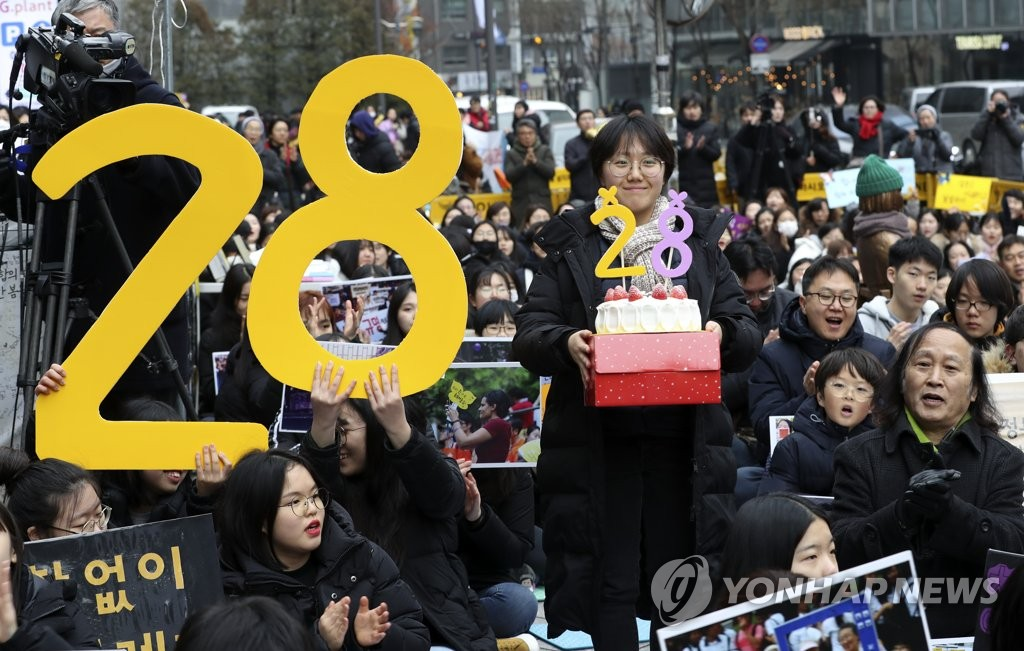 Participants hold up signs and a cake marking the 28th anniversary of the weekly rally held every Wednesday to protest against Japan's sexual slavery of Korean women during World War II on Jan. 8, 2020. (Yonhap)