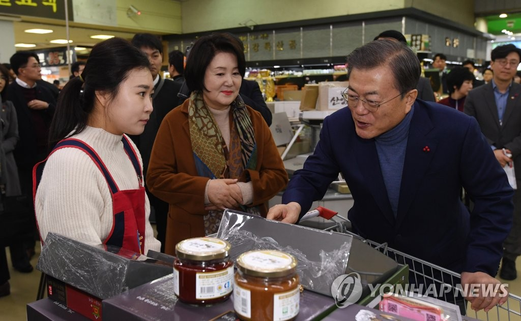 President Moon Jae-in (R) and first lady Kim Jung-sook (C) visit a farmers market in southern Seoul on Jan. 23, 2020, a day before the start of the Lunar New Year holiday season. (Yonhap)