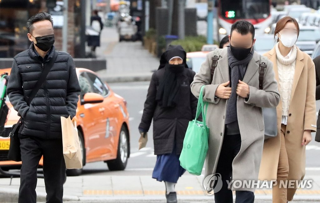 Citizens in Seoul wearing face masks cross a street amid growing concern about the spread of a new coronavirus on Jan. 28, 2020. (Yonhap)
