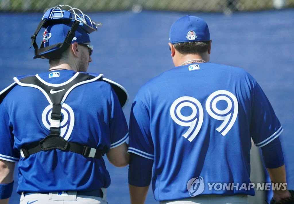 Toronto Blue Jays' catcher Danny Jansen (L) and pitcher Ryu Hyun-jin talk during their bullpen session at the Player Development Complex outside TD Ballpark in Dunedin, Florida, on Feb. 16, 2020. (Yonhap)