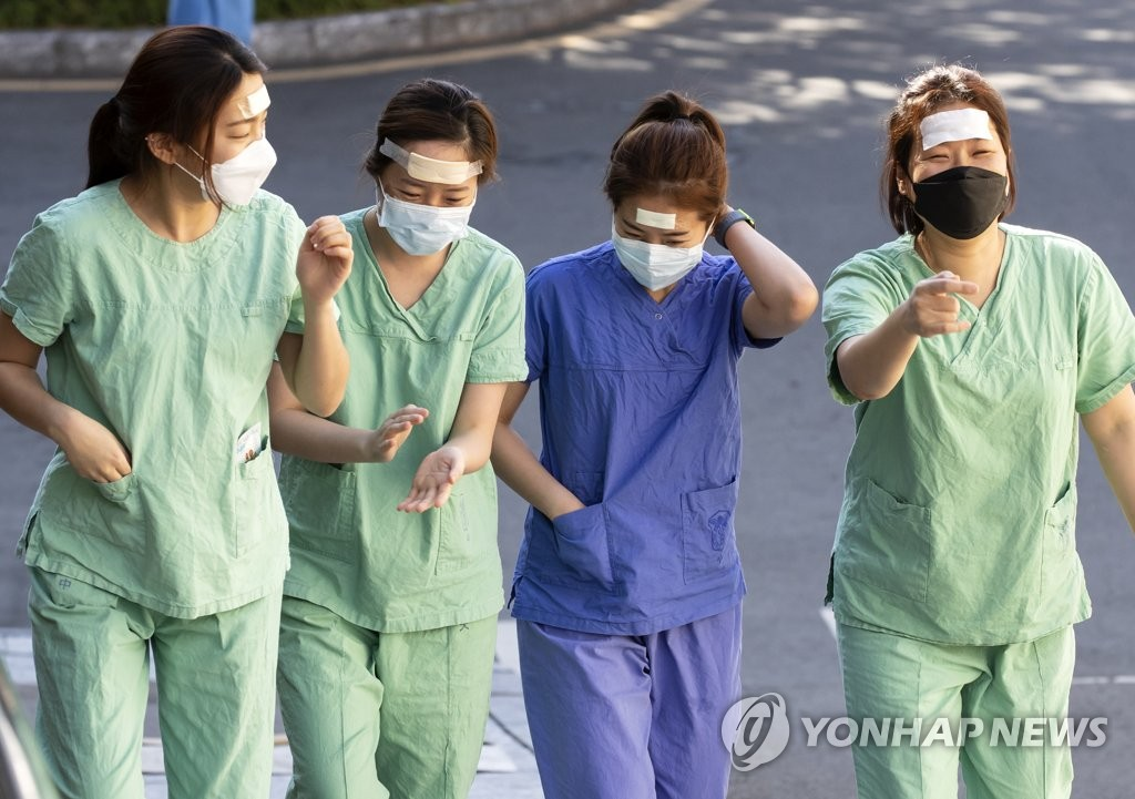 Medical staffers walk to a staff lounge after finishing a shift at Dongsan Hospital in coronavirus-hit Daegu, 302 kilometers southeast of Seoul, on March 11, 2020. (Yonhap)