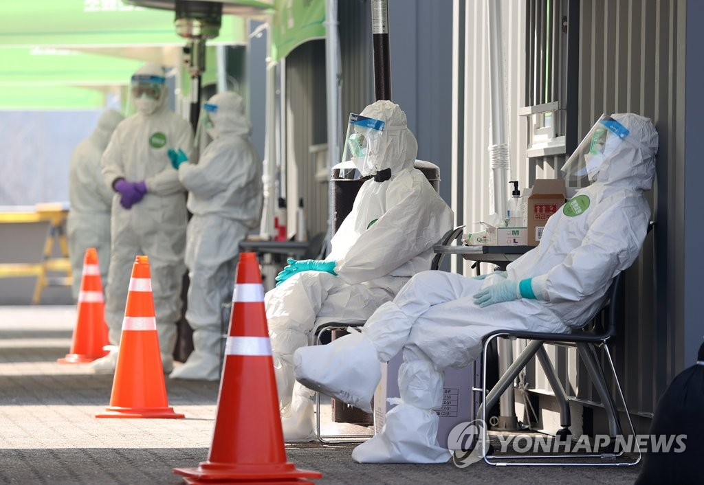 Medical workers wearing protective gear take a rest at a drive-through testing facility in Seoul on March 18, 2020. (Yonhap)