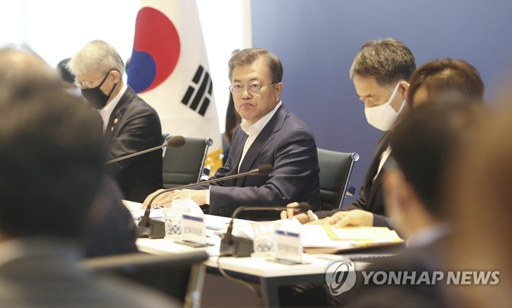 President Moon Jae-in (C) is briefed on the progress for developing medicine and vaccines for the new coronavirus at a joint meeting among industry, academia, research institutes and hospital officials at Institute Pasteur Korea in Seongnam, south of Seoul, on April 9, 2020. (Yonhap)
