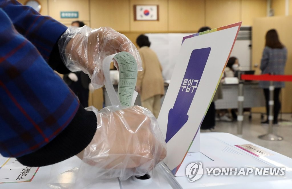A voter casts a ballot in early voting for the April 15 parliamentary elections at a polling station in the southeastern Seoul ward of Gangnam on April 10, 2020. (Yonhap)