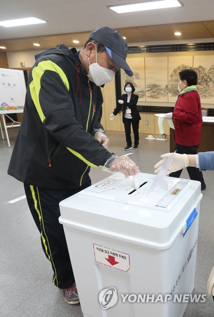 A voter wearing plastic gloves casts his ballot at a polling station in the city of Jeju on South Korea's largest island of the same name on April 15, 2020, as South Koreans began voting the same day to elect a new parliament amid the outbreak of the new coronavirus. (Yonhap)