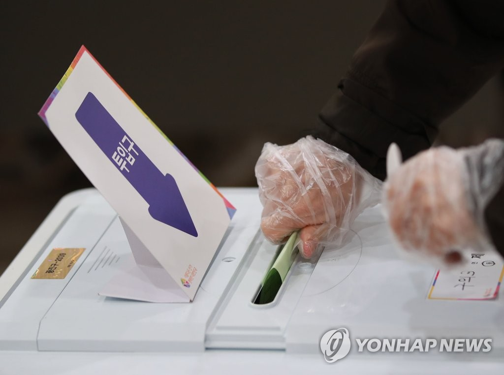 A voter wearing plastic gloves casts his ballot at a polling station in Seoul's Gwangjin Ward on April 15, 2020, as South Koreans began voting the same day to elect a new parliament amid the outbreak of the new coronavirus. (Yonhap)