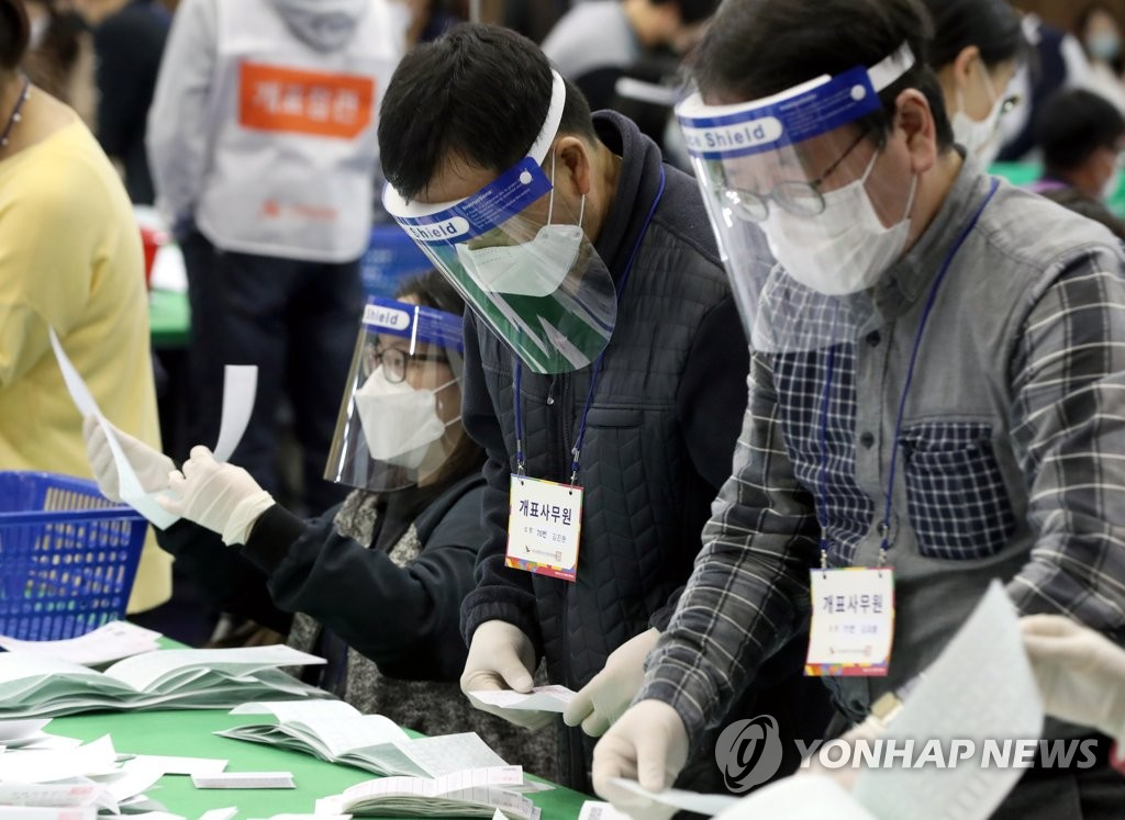 Officials wearing protective face guards, masks and plastic gloves go through ballots at a middle school stadium in the southern port city of Busan on April 15, 2020. (Yonhap)