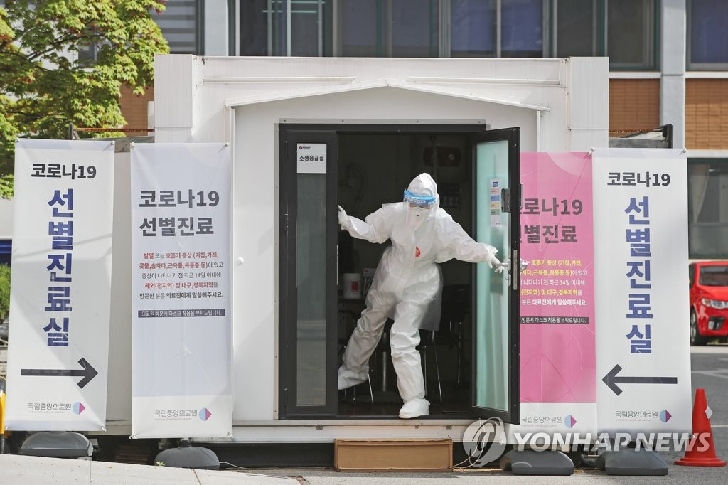 Medical workers get ready for work at a hospital in central Seoul on April 21, 2020. (Yonhap)