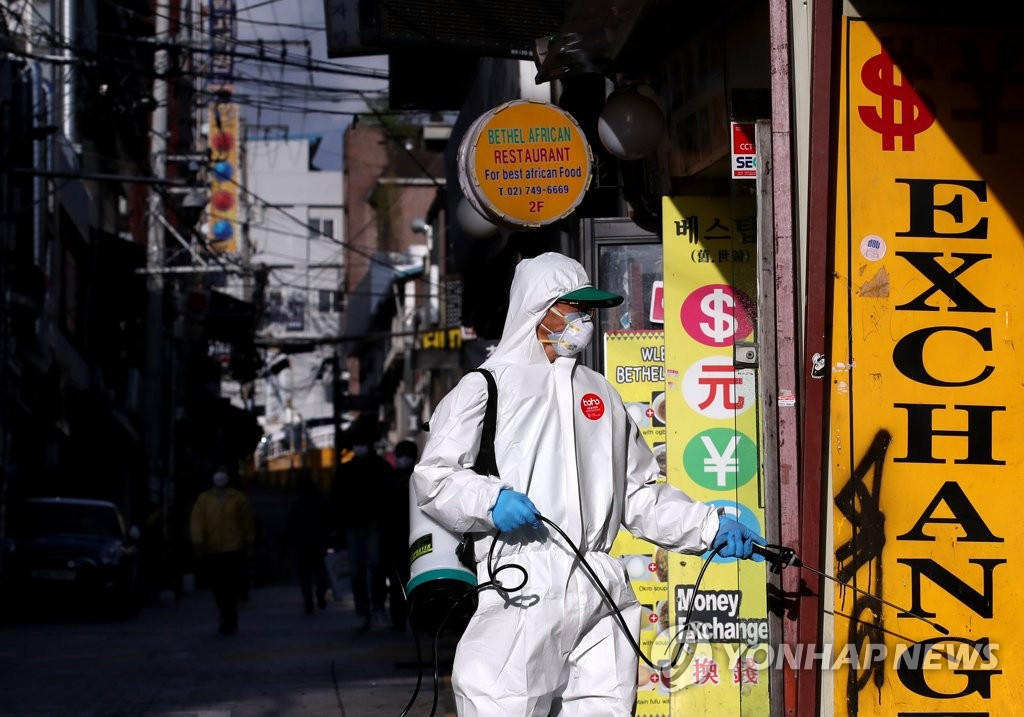 Volunteer workers disinfect a storefront at a street in the central Seoul neighborhood of Itaewon on May 12, 2020. (Yonhap)