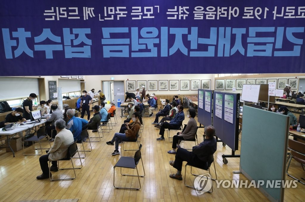 Residents wait while keeping a distance from each other to apply for emergency disaster relief funds at a community center in Seoul on May 18, 2020. The state funds for everyone in the country are designed to help activate the economy, especially small business sectors, amid the coronavirus crisis. (Yonhap)
