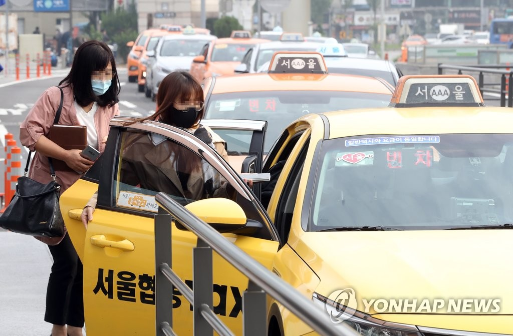 Two people wearing face masks get in a taxi in front of Seoul Station in central Seoul on May 26, 2020. (Yonhap)