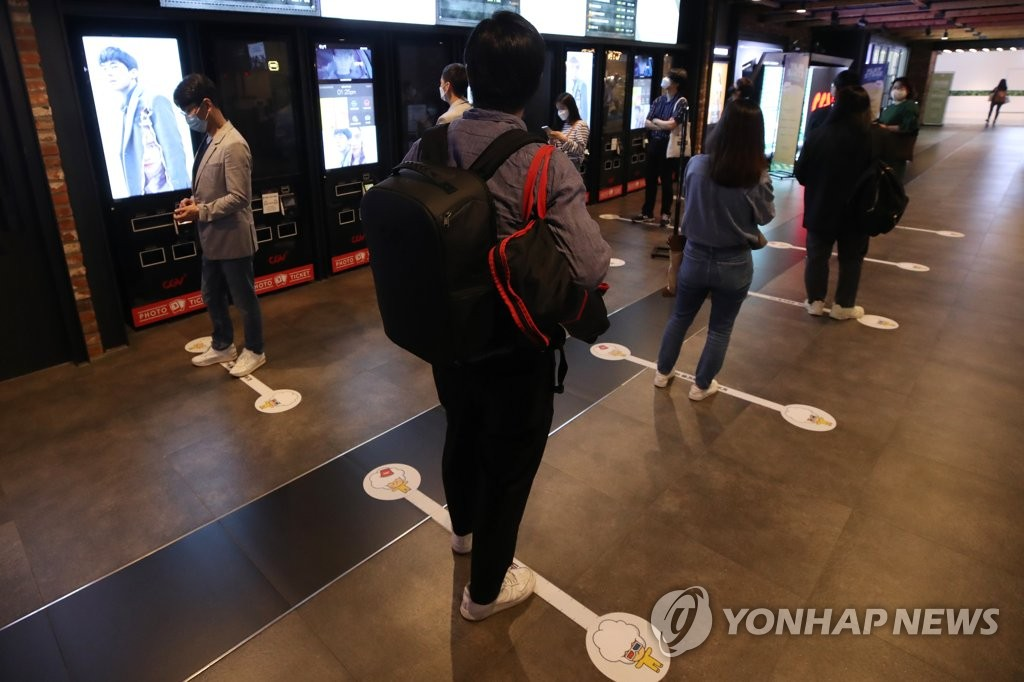 Journalists line up at a distance from one another to get tickets to a movie event at a cinema in Seoul on June 4, 2020. (Yonhap)