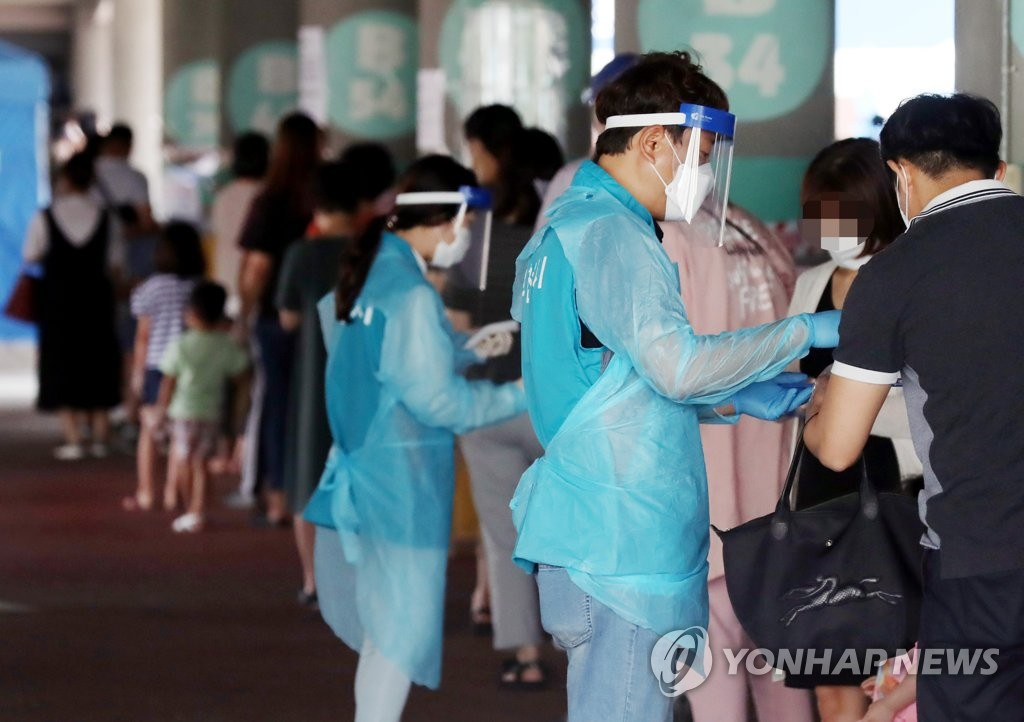 Citizens form a long line to receive new coronavirus tests at a testing site outside Bucheon Stadium, west of Seoul, on June 10, 2020. (Yonhap)