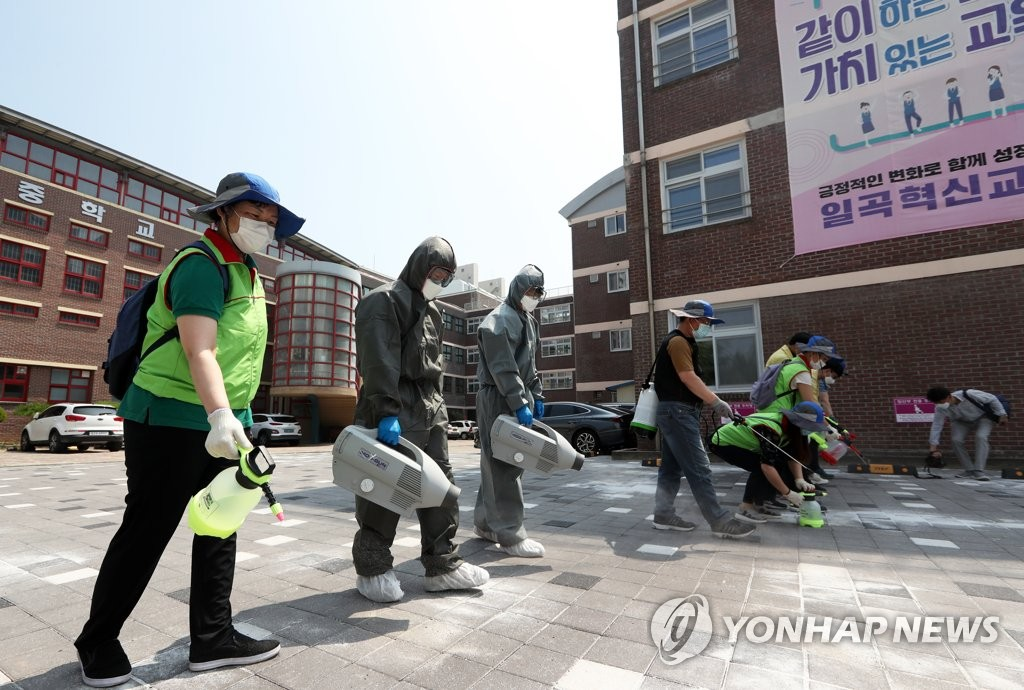 In this file photo, taken on June 22, 2020, quarantine officials disinfect a school in Gwaungju, some 330 kilometers south of Seoul. (Yonhap)