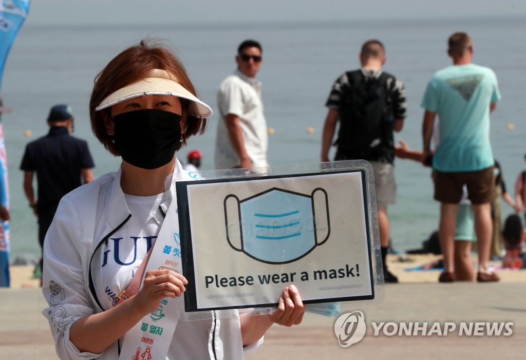 An official in the southeastern port city of Busan holds a sign that asks visitors to wear masks at the city's Haeundae Beach on July 5, 2020. (Yonhap)