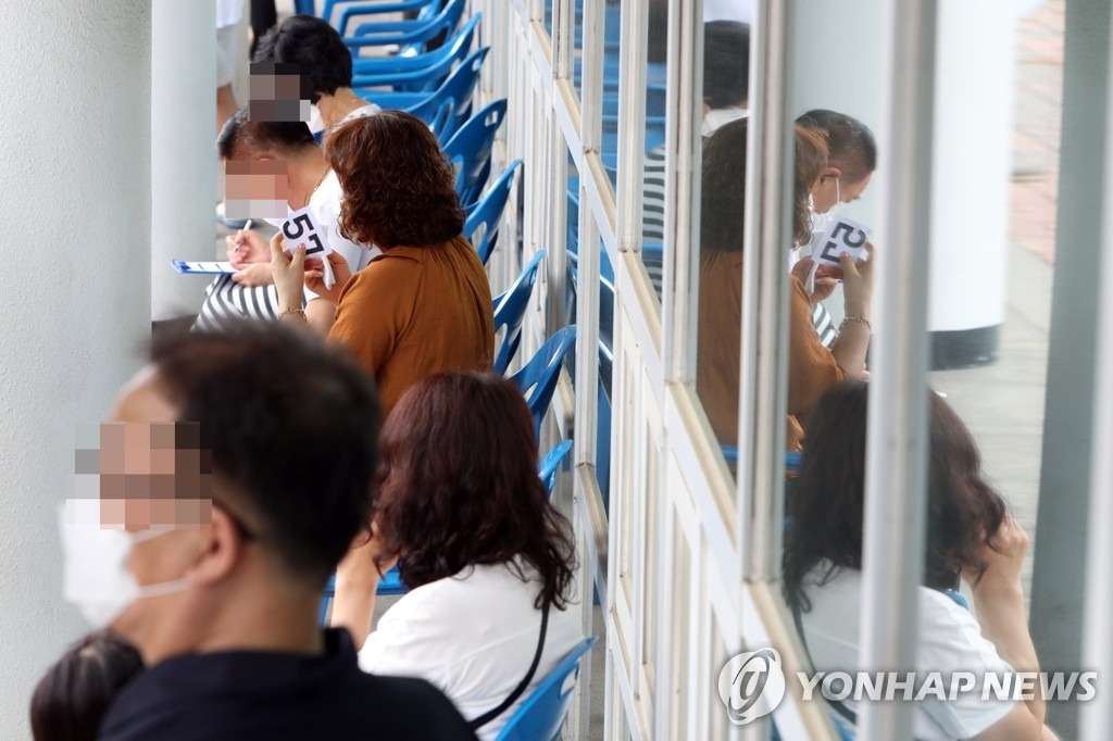 Citizens wait in line while holding number tickets to receive new coronavirus tests in Gwangju, 330 kilometers south of Seoul, on July 7, 2020. (Yonhap)
