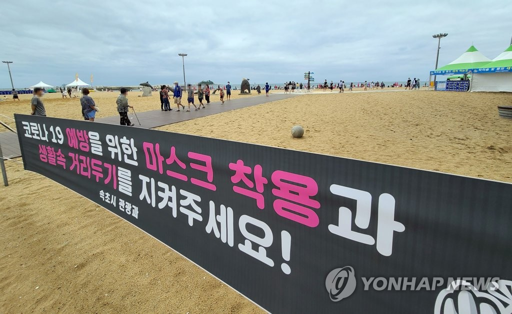 A banner calls for the use of face masks and keeping a safe distance at a beach in the eastern city of Sokcho on July 11, 2020, in an effort to stem the spread of the new coronavirus. (Yonhap)