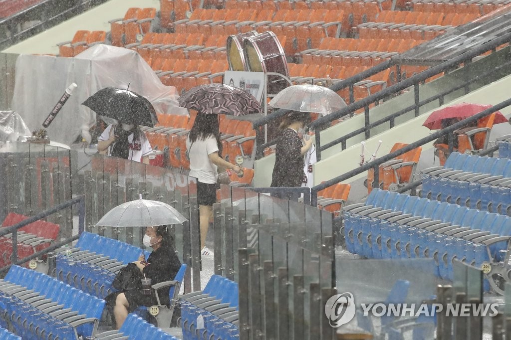 In this file photo from July 29, 2020, fans leave Jamsil Baseball Stadium in Seoul during a rain delay in a Korea Baseball Organization regular season game between the home team Doosan Bears and the Kiwoom Heroes. (Yonhap)