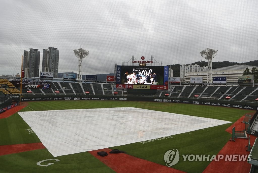 The field at Sajik Stadium in Busan, 450 kilometers southeast of Seoul, is covered in a tarp before the start of a Korea Baseball Organization regular season game between the home team Lotte Giants and the NC Dinos on Aug. 11, 2020. (Yonhap)