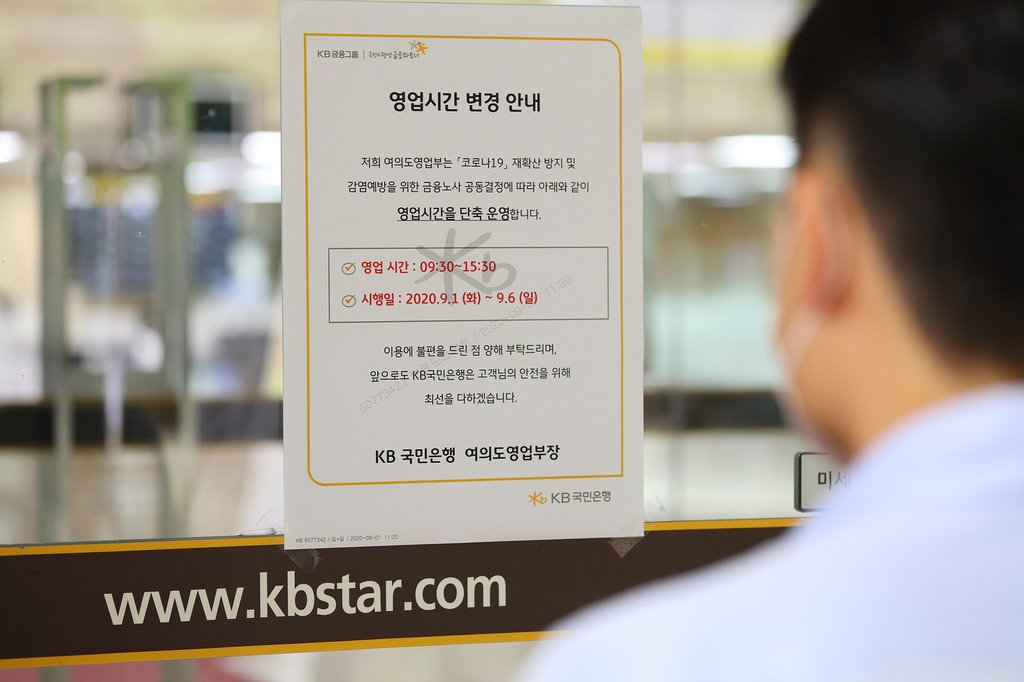 A visitor looks at a notice informing customers of the shortening of business hours by one hour at a KB Kookmin Bank branch in Seoul on Sept. 1, 2020. The step was taken at banks in Seoul and its satellite cities to prevent the spread of COVID-19. The operation hours are from 9:30 a.m. to 3:30 p.m. (Yonhap)