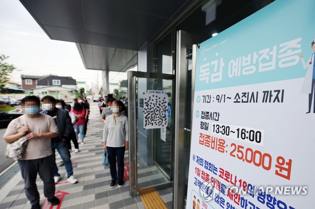 In this file photo from Sept. 23, 2020, people line up outside the headquarters of the Gwangju office for the Korea Association of Health Promotion in Gwangju, 330 kilometers south of Seoul, to receive flu vaccines. (Yonhap)