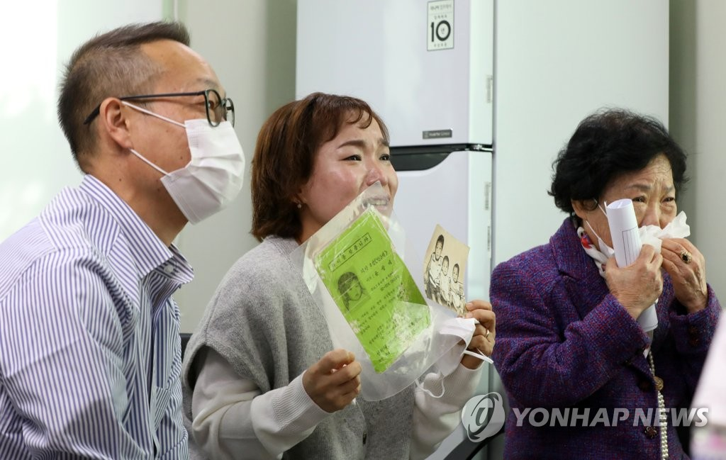 Yoon Sang-hee (C), twin sister of Yoon Sang-ae, a Korean-born adoptee who is now an American citizen, holds a photo and a poster during a reunion held via a video call in Seoul on Oct. 15, 2020, 44 years after the younger Yoon went missing. Next to Yoon is their older brother Yoon Sang-myung (L) and mother Lee Eung-soon. (Yonhap)