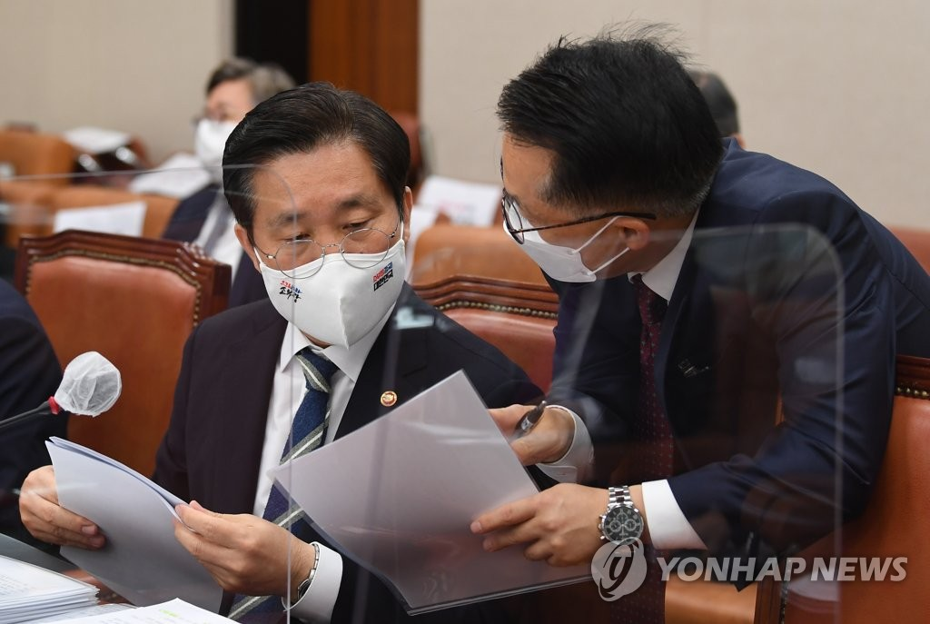 Industry Minister Sung Yun-mo (L) prepares for a parliamentary session at the National Assembly in western Seoul on Oct. 22, 2020. (Yonhap)
