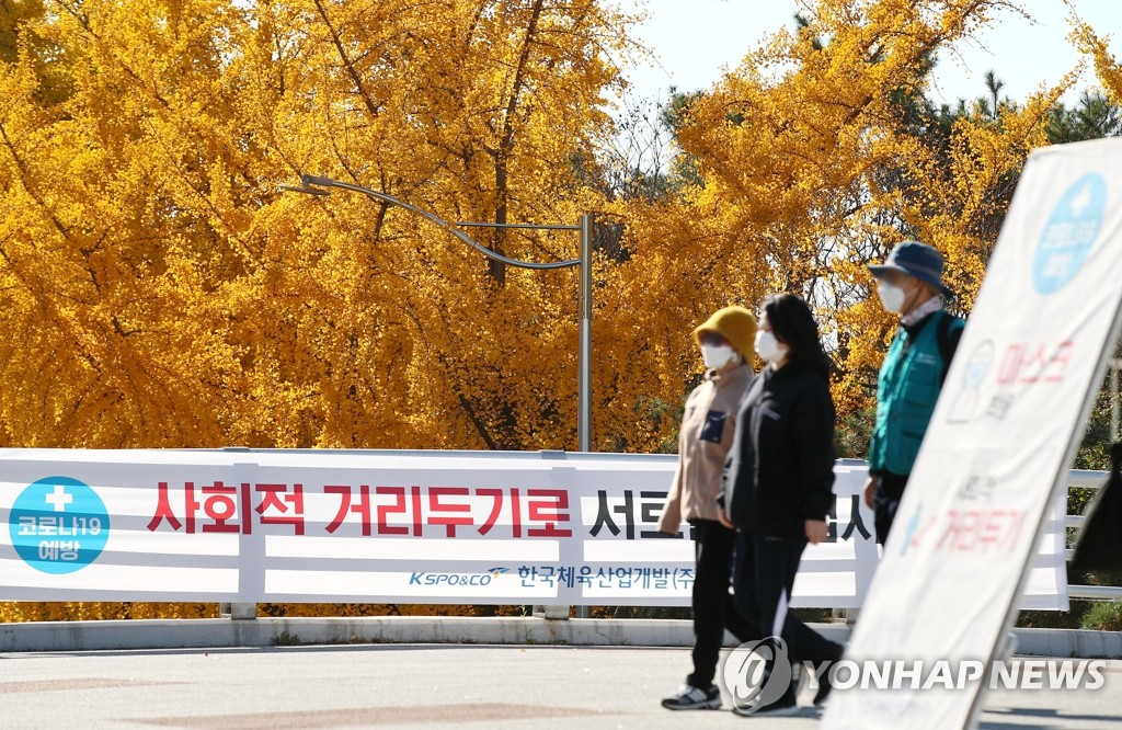 Citizens wearing protective masks walk around a park in eastern Seoul on Nov. 8, 2020. (Yonhap)