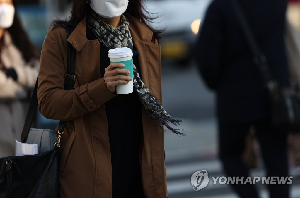 A commuter wearing a protective mask walks near Gwanghwamun Square in central Seoul on Nov. 9, 2020. (Yonhap)