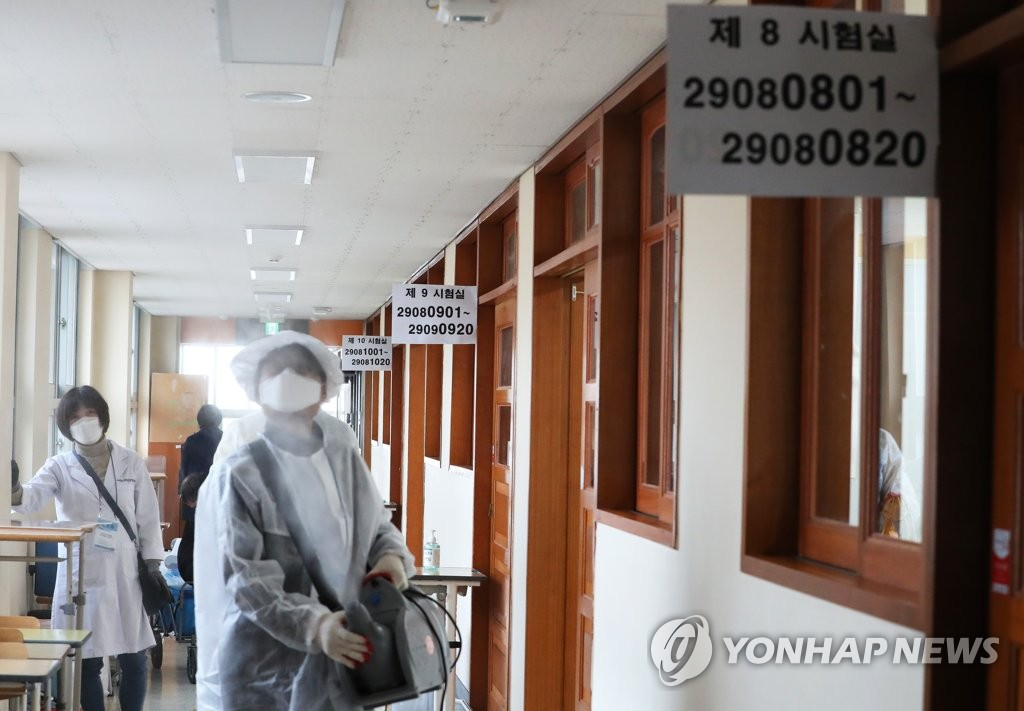Health workers disinfect a school in the central city of Sejong on Dec. 2, 2020 amid a resurgence of the coronavirus ahead of the national college entrance exam slated for Dec. 3. (Yonhap)